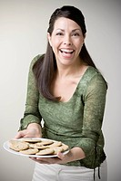 Hispanic woman holding plate of cookies