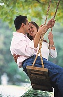 Young Asian couple on swing