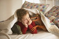 Young boy under covers in bed with toy dinosaurs