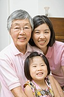Asian grandmother with daughter and granddaughter smiling