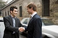 Two Hispanic businessmen shaking hands in street