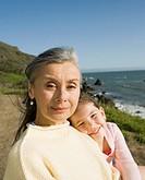 Grandmother and granddaughter hugging at ocean