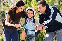 Hispanic parents helping daughter ride bicycle