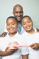African male dentist with twin boys holding toothbrush and model of teeth
