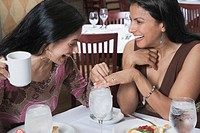 Hispanic woman showing ring to friend at restaurant