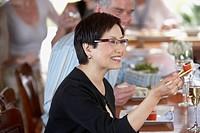 Asian woman eating sushi at bar