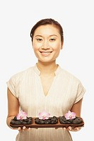 Asian woman holding spa treatment tray