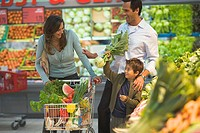 Family at supermarket vegetable counter