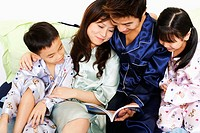 Close-up of a mid adult man and a young woman with their children reading a book on the bed