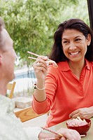Close-up of a mature woman feeding a mature man with chopsticks