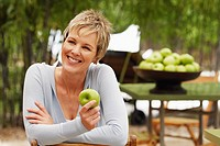 Close-up of a mature woman holding a granny smith apple and smiling