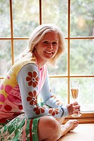 Portrait of a mature woman holding a champagne flute and smiling
