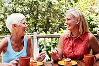 Two mature women sitting at the table with plates of dessert in front of them and smiling