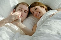 Young adult couple together in bed looking at hands