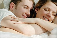 Young couple cuddling together in bed smiling