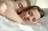 Young couple in bed sleeping and cuddling together