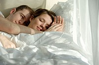 Young couple cuddling in bed together