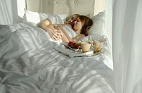 Young couple in bed cuddling with tray of breakfast foods