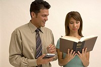 Portrait of a man using his palm pilot while a woman reads a book