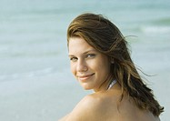 Young woman on beach, smiling over shoulder at camera