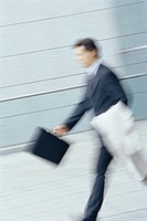 Businessman walking with briefcase and jacket over arm, blurred motion