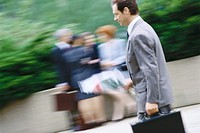 Businessman carrying bouquet of flowers and briefcase
