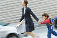 Businesswoman hurrying, holding little boy´s hand