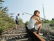 Man on woman playing golf on railway track