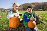 Boy and girl in field with pumpkins