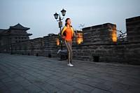 Young Woman Jogging Along City Wall