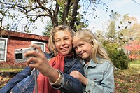 Two Girls Using Digital Camera Outdoors