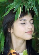 Woman standing amongst leaves, head and shoulders