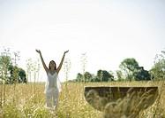 Woman standing in sun salutation pose, in field