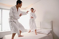 Couple standing on bed, practicing Kung Fu