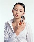 Young woman spraying perfume on herself