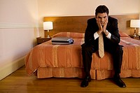 Businessman resting his chin in his hands in hotel room
