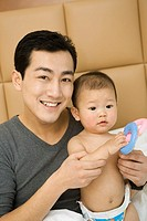 Man playing with his baby in bed