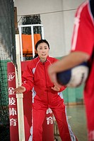 Female athletic coach instructing male volleyball player
