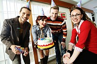 Two businessmen and two businesswomen celebrating a birthday