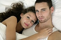 Portrait of a young couple lying in bed