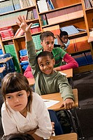 Boy raising his hand in a classroom