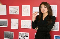 Portrait of a businesswoman standing in front of designs on a wall