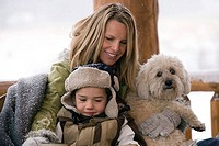 Mature woman sitting with her son and holding a dog