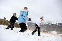 Mature woman having a snowball fight with her son and daughter
