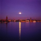 City across the river with a moon shinning above in the sky