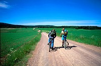 Two person cycling on the path through open fields