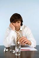 Man holding pill, sitting on desk