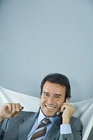 Businessman using cell phone and holding cigar, smiling at camera
