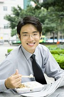 Businessman eating lunch with chopsticks and reading newspaper, smiling at camera