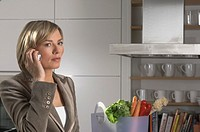 portrait of young businesswoman standing in kitchan and talking on mobile phone